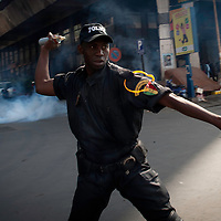 Police throws  tear gas can to disperse anti-government protesters and bystanders, in central Dakar, Senegal Friday, Feb. 17, 2012. Anti-government protesters and police clashed for a third consecutive day Friday, engaging in running street battles of rock throwing and tear gas in the streets of Dakar's downtown Plateau neighborhood. Demonstrators are defying a government ban on protests to call for the departure of 85-year-old President Abdoulaye Wade, who is running for a third term in next week's election