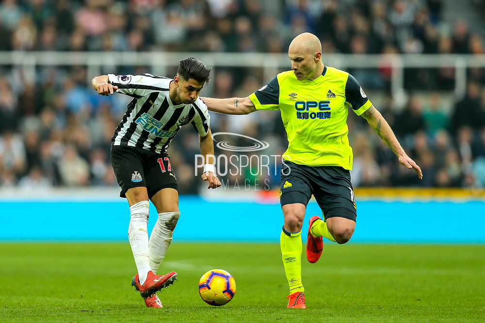 Ayoze Perez (#17) of Newcastle United passes the ball under pressure from Aaron Mooy (#10) of Huddersfield Town during the Premier League match between Newcastle United and Huddersfield Town at St. James's Park, Newcastle, England on 23 February 2019.
