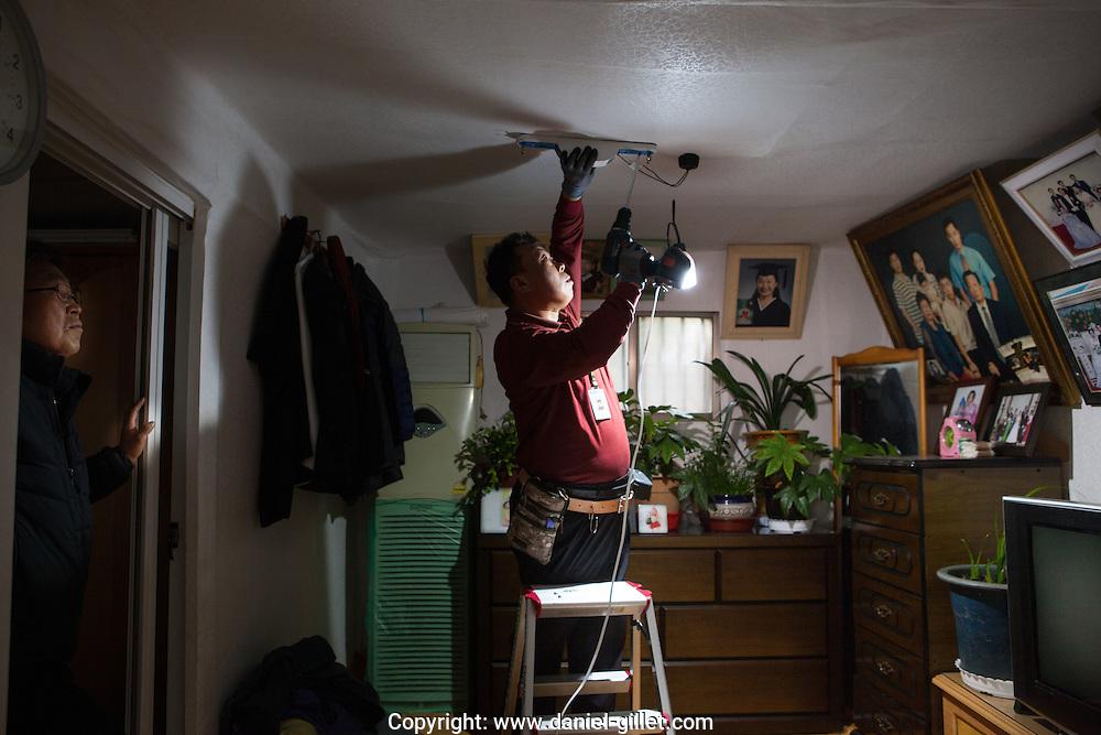 Un électricien de la mairie de Séoul installe une lampe LED dans une logement à bas revenus. Village de BukJung, Séoul, Corée du Sud. // An electrician from Seoul Metropolitan Government installs a LED light in a low income house, BukJung Village, Seoul, South Korea. November 2015.