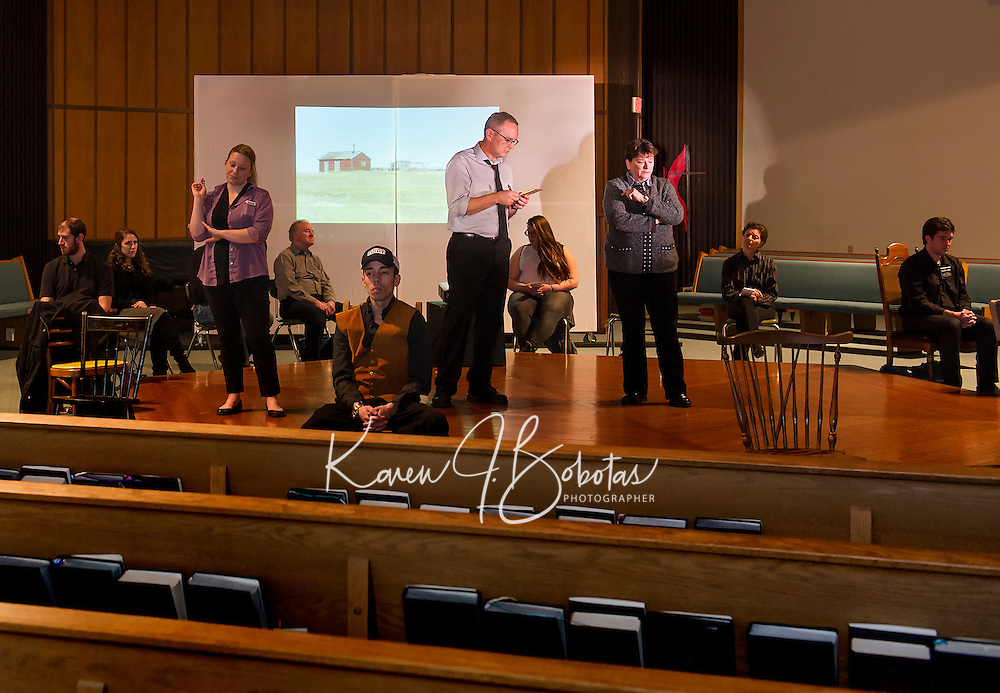 Hillary Ayers, Aaron Witham and Lynn T. Dadian standing in center stage surrounded by cast members (l-r) Frank Stetson II, Emily Getchell-Lacey, Peter Ayers, Rachael McCarthy, Sandy McLaughlin and Mark Lambert at the United Methodist Church surrounded by the cast of The Laramie Project performed by the Streetcar Company during dress rehearsal on Tuesday evening.   (Karen Bobotas/for the Laconia Daily Sun)