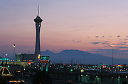 Stratosphere tower and lights against the mountains at sunset Las Vegas