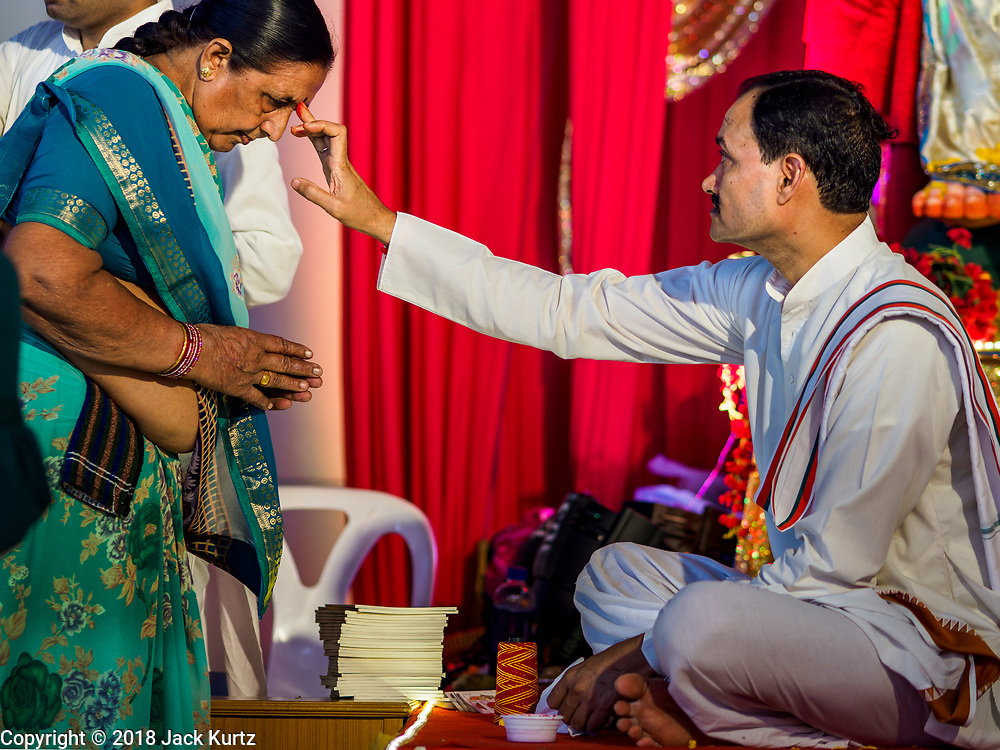 """23 SEPTEMBER 2018 - BANGKOK, THAILAND:  A Hindu priest gives a woman a """"talika"""" at the Ganesha Festival at Wat Dan in Bangkok. Ganesha Chaturthi also known as Vinayaka Chaturthi, is the Hindu festival celebrated on the day of the re-birth of Lord Ganesha, the son of Shiva and Parvati. The festival, also known as Ganeshotsav (""""festival of Ganesha"""") is observed in the Hindu calendar month of Bhaadrapada, starting on the the fourth day of the waxing moon. The festival lasts for 10 days, ending on the fourteenth day of the waxing moon. Outside India, it is celebrated widely in Nepal and by Hindus in the United States, Canada, Mauritius, Singapore, Thailand, Cambodia, and Burma.   PHOTO BY JACK KURTZ"""