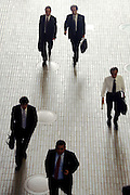 overhead view of businessmen walking in a hallway in a large office building Tokyo Japan