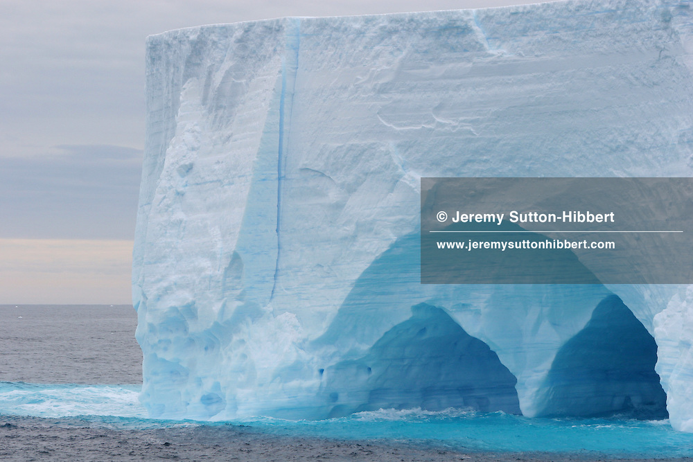 Icebergs, with ice caves, in the Southern Ocean, off the coast of Antarctica.
