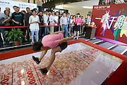 NANJING, CHINA - MAY 08: (CHINA OUT) <br /> <br /> Buyers Participate In Long Jump To Get Discount <br /> <br /> A man take part in the standing long jump at a sales office  in Nanjing, Jiangsu Province of China. A long jump runway was filled with cashes and the jumping distance became the measure of the discount level, which was set into different tiers of coupon for the real estate purchasing. The farther buyers jump, the more subsidy they will get. The highest coupon can be as much as 100,000 yuan, attracting hundreds of buyers. <br /> ©Exclusivepix