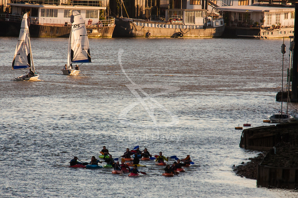 Battersea, London, April 29th 2015. After a day that started off with gloomy, damp weather, Londoners are rewarded with a beautiful spring sunset. PICTURED: A group of kayakers paddles downstream as two yachts tack in the evening breeze.