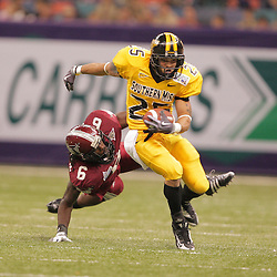 21 December 2008:  Southern Miss running back Damion Fletcher (25) breaks a tackle by Troy defensive back Sherrod Martin (6) during the first half of the R+L Carriers New Orleans Bowl between the Southern Mississippi Golden Eagles and the Troy Trojans at the New Orleans Superdome in New Orleans, LA.