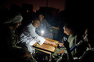 Idle tour guides use their cell phones for light play as they play backgammon at a cafe during a power cut on June 18, 2013 in Luxor, Egypt. Egyptians working in the tourism industry have lost work since the revolution in 2011 and blackouts have been increasing in the midst of Egypt's energy crisis. Ann Hermes/© The Christian Science Monitor 2013