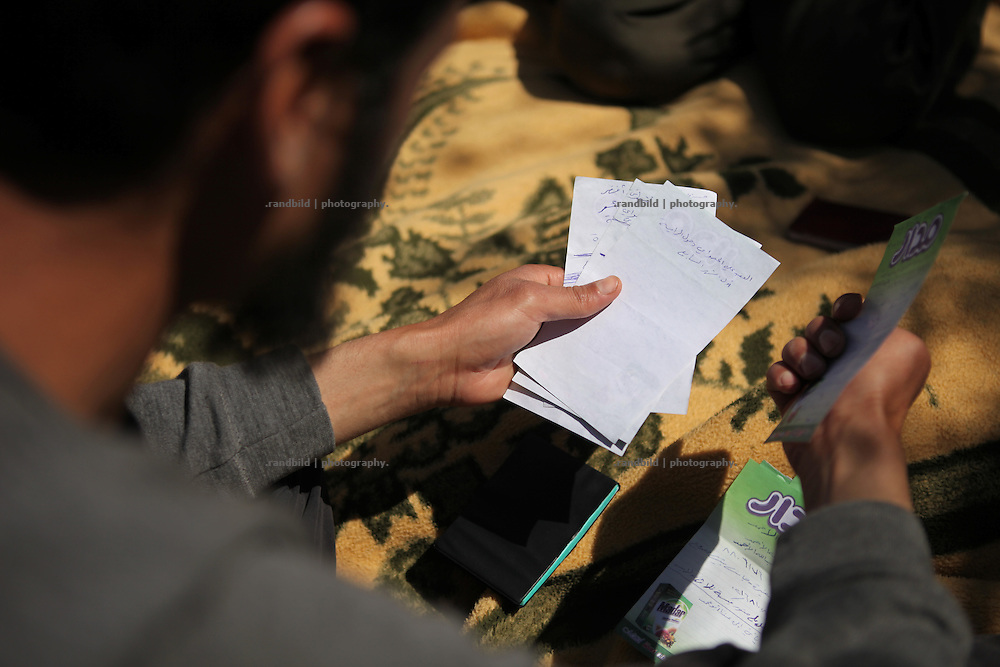 Walid Dabbas holds some paper sheets in his hands containing lists of names of army officers and soldiers he accused of commited war cirmes.