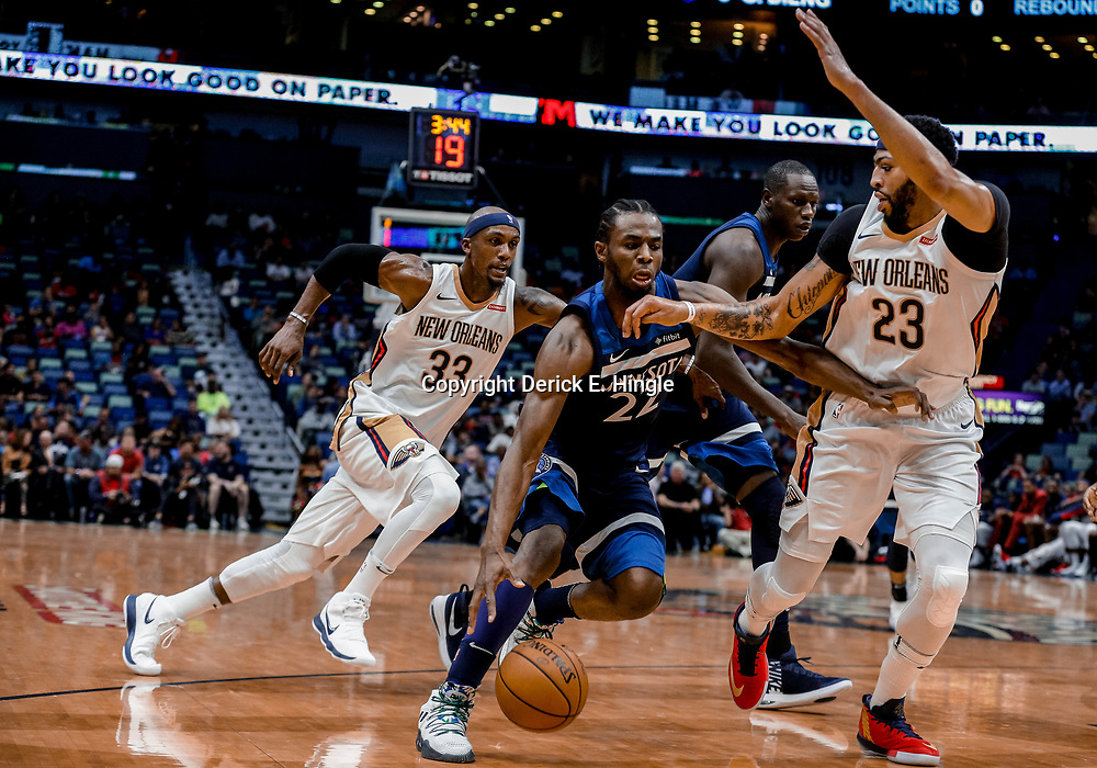 Nov 1, 2017; New Orleans, LA, USA; Minnesota Timberwolves forward Andrew Wiggins (22) drives past New Orleans Pelicans forward Dante Cunningham (33) and forward Anthony Davis (23) during the first quarter of a game at the Smoothie King Center. Mandatory Credit: Derick E. Hingle-USA TODAY Sports