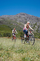 Two teenage girls and boy (16-17 years) biking mountain in background