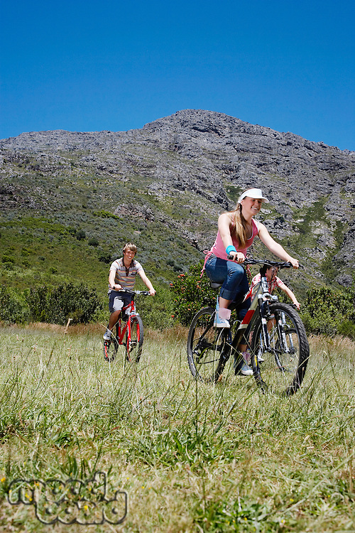 Two teenage girls and boy (16-17 years) biking mountain in background