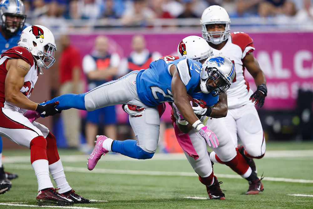 Detroit Lions running back Ameer Abdullah (21) is stopped by Arizona Cardinals free safety Tyrann Mathieu, left, and strong safety Deone Bucannon, right, during the first half of an NFL football game, Sunday, Oct. 11, 2015, in Detroit. (AP Photo/Rick Osentoski)