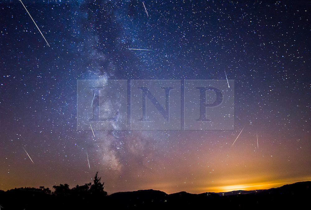 © Licensed to London News Pictures.13/08/2013. Orcas Island, USA.  A stunning composite image compromising of 10 single images showing Perseid meteors falling infront of The Milky Way over Orcas Island in Washington, USA taken by photographer Astrophotographer Cody Limber from the deck of his property. Photo credit: Cody Limber/LNP