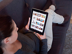 Woman using iPad computer tablet at home to look at Youtube internet website
