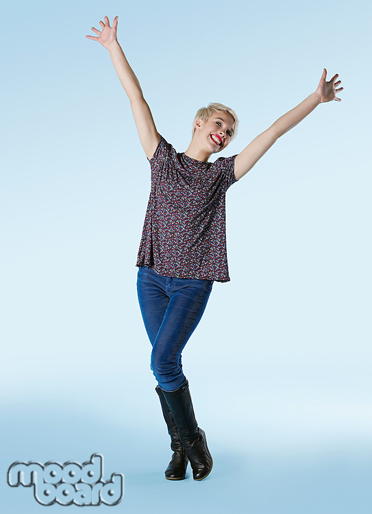 Young woman standing with arms outstretched and laughing