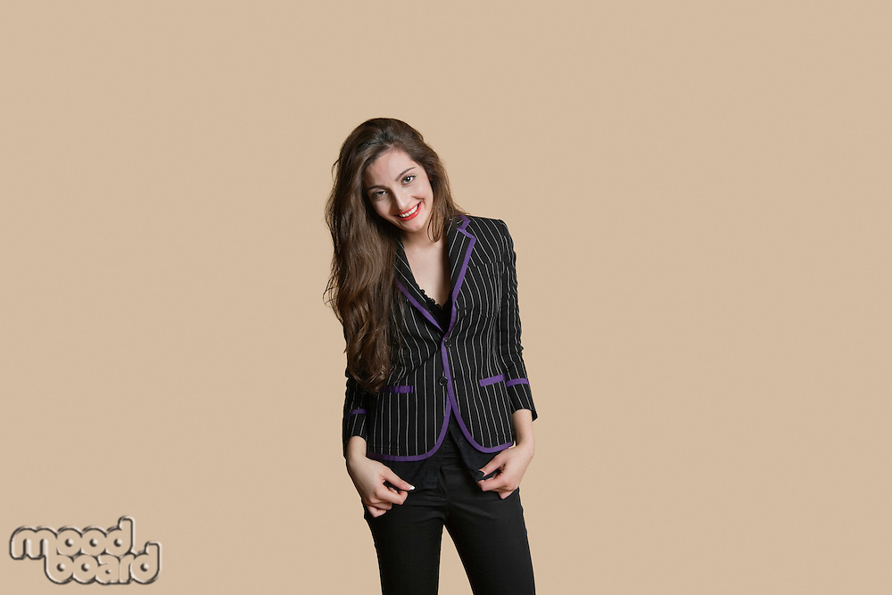 Portrait of beautiful young woman in formals over colored background