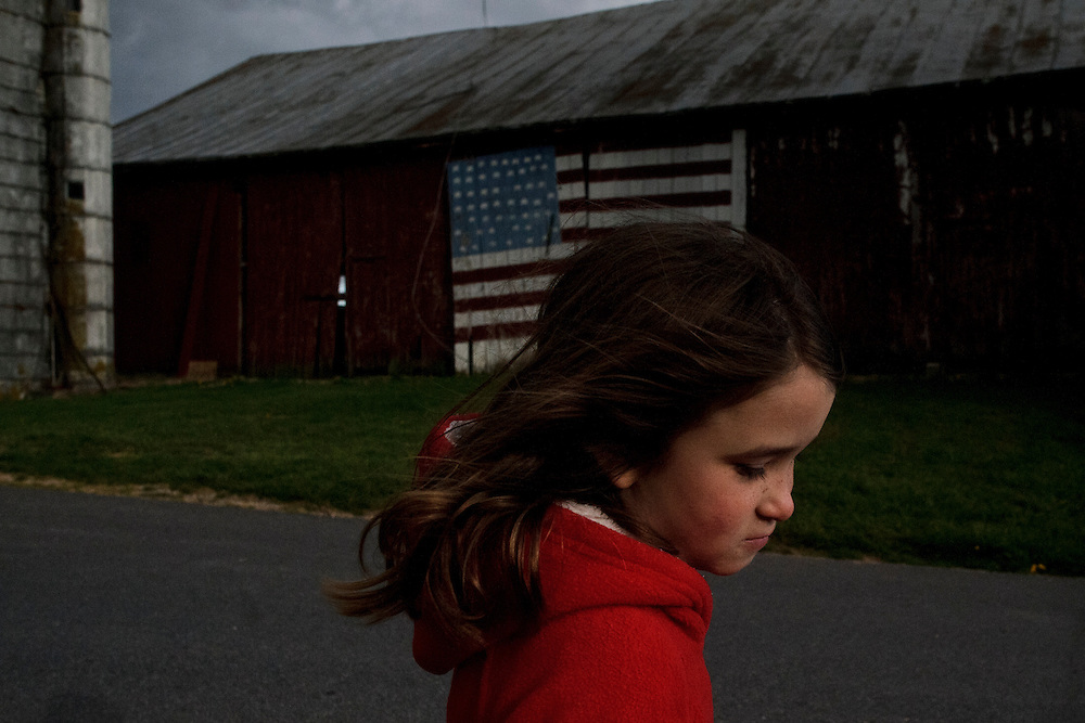photo by Matt Roth.Wednesday, April 11, 2012..Rory Shriver walks past her grandparents' barn door. Ron Shriver's family painted the U.S. flag in honor of Ron a few weeks before he left for bootcamp -- in the summer of 2001...Ron Shriver grew up on a large farm house in Pleasant Valley, Maryland, a small township outside Westminster. After his lease was up, he moved back to his parent's home with his two children Rory and Miles, living temporarily in their basement before graduating from McDaniel College in May. After tossing his graduation cap, he and his children will drive cross country to meet up with his wife who has been working on her graduate degree in Alaska. ..Ron Shriver is a retired marine staff sergeant. He is also the first in his family to attend college, thanks to the New G.I. Bill. His wife, a fellow retired Marine, is finishing up graduate school in Alaska. After Ron gets his undergraduate degree from McDaniel College in May, he plans to drive to Alaska with is two children Rory, 6, and Miles, 5. For the move Ron got rid of most of his family's belongings, and after his lease was up, he and his children moved back into his parent's farmhouse.