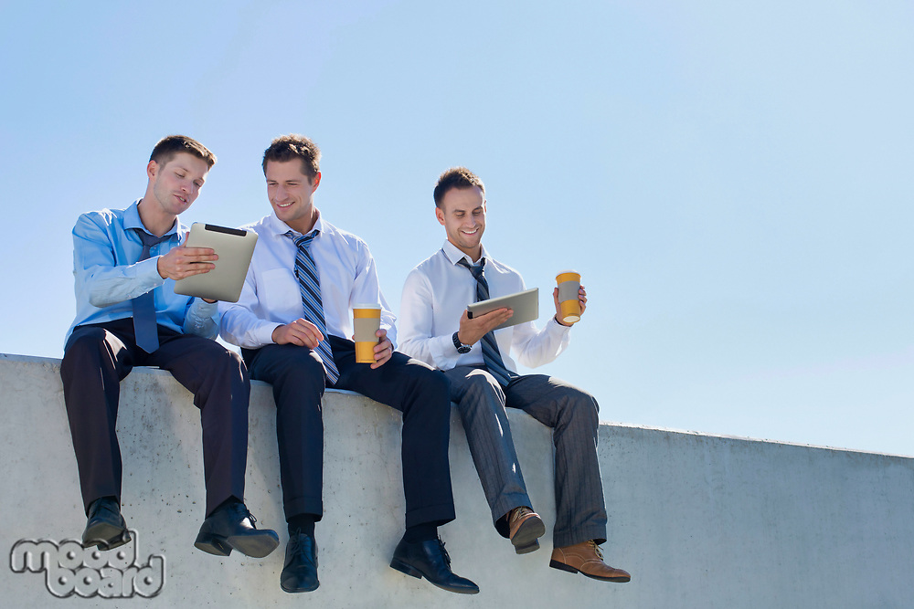 Photo of thoughtful businessmen sitting while using digital tablet in office rooftop