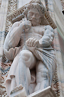 Milan, Italy, Duomo Cathedral. Marble male statue supporting a pedestal - he's looking down toward the ground.