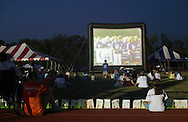 Goshen, New York - People sit around the track, which is lined with luminaria in remembrance of cancer victims, and on the grass to watch a video projected onto a large screen during the Relay for Life at Goshen High School on June 19, 2011. The Relay for Life is the American Cancer Society's signature fundraising event. Participants celebrate the lives of people who have battled cancer, remember loved ones lost, and fight back against the disease by raising money.
