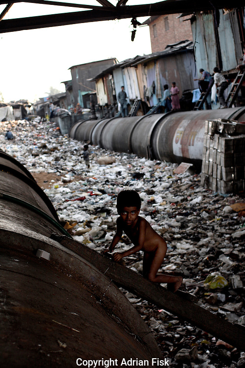 A child climbs the ladder that acts as a route between the pipes on 21st Oct 2006. These pipes carry Bombays water into the city, but for most of Dharavi citizens there is no access to clean drinking water.