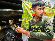 14 JULY 2015 - THAILAND:  A Thai soldier pumps water from an army water truck to a private home in Pathum Thani province near Bangkok. The drought that has crippled agriculture in central Thailand is now impacting residential areas near Bangkok. The Thai government is reporting that more than 250,000 homes in the provinces surrounding Bangkok have had their domestic water cut because the canals that supply water to local treatment plants were too low to feed the plants. Local government agencies and the Thai army are trucking water to impacted communities and homes. Roads in the area have started collapsing because of subsidence caused by the retreating waters. Central Thailand is contending with drought. By one estimate, about 80 percent of Thailand's agricultural land is in drought like conditions and farmers have been told to stop planting new acreage of rice, the area's principal cash crop.      PHOTO BY JACK KURTZ