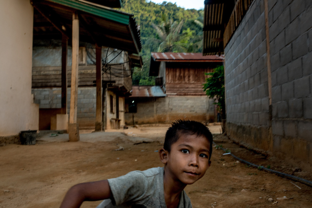 A boy in the village of Khoc Kham. The village is not connected to the main electrical grid and many residents operate their own turbines to power lights and sometimes small appliances.