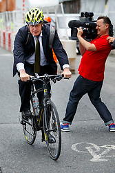 © Licensed to London News Pictures. 06/08/2014. LONDON, UK. Mayor of London, Boris Johnson leaving Bloomberg HQ in central London on his bike after delivering a speech on Europe and confirming intention to stand as an MP for the Conservative Party at the next general election. Photo credit : Tolga Akmen/LNP
