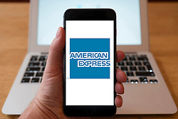 Using iPhone smartphone to display logo of American Express the multinational financial services corporation