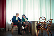 Elderly couple smiling and laughing with each other in a Miami Beach hotel lobby