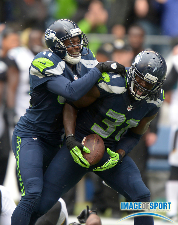 Sep 22, 2013; Seattle, WA, USA; Seattle Seahawks safety Kam Chancellor (31) celebrates with cornerback Byron Maxwell (41) after intercepting a pass in the fourth quarter against the Jacksonville Jaguars at CenturyLink Field. The Seahawks defeated the Jaguars 45-17.