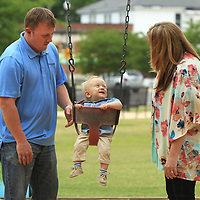Brad and Alice Griggs play with their 14 month old son Colton on the swing at Fairpark in Tupelo.