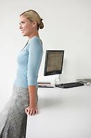 Woman leaning on desk in office side view