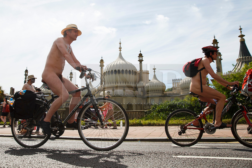© Licensed to London News Pictures. 08/06/2014. BRIGHTON, UK. Nude protesters going past the Royal Pavilion in Brighton on Sunday 8 June 2014 as part of the World Naked Bike Ride, which aims to raise awareness of cyclists on the roads and in the traffic. Photo credit : Tolga Akmen/LNP