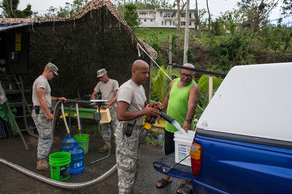 Comerio, PR, November 11, 2017--Luis Durán Vega collects 50 gallons of water from a water purification station set up near Comerio, PR by the National Guard.  Duran makes the 20 minute drive every other day for water for his family of five every two days. The National Guard division 139 BSB is from South Dakota and have been in Puerto Rico since October 8th. This station distributes 40,000 - 60,000 gallons a day in Comerio. Photo by Lori Waselchuk/BRAF