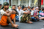 """11 MAY 2013 - BANGKOK, THAILAND:   Farmers sit in the road in front of Government House. Several hundred small scale family farmers camped out """"Government House"""" (the office of the Prime Minister) in Bangkok to Thai Prime Minister Yingluck Shinawatra to deliver on her promises to improve the situation of family farmers. The People's Movement for a Just Society (P-move) is a network organization which aims strengthen the voices of different, but related causes working to bring justice for marginalized groups in Thailand, including land rights for small-scale farmers, citizenship for stateless persons, fair compensation for communities forced to relocate to accommodate large scale state projects, and housing solutions for urban slum dwellers, among others.   PHOTO BY JACK KURTZ"""