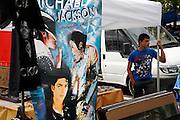 Jeune vendeur du marché folklorique à Bulle, junger Verkäufer am Wochenmarkt im Sommer in Bulle mit Michael Jackson Poster und Stoffen. © Romano P. Riedo