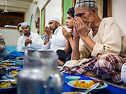 26 JULY 2013 - BANGKOK, THAILAND:   A man prays before eating the Iftar meal at Haroon Mosque in Bangkok. Iftar is the Muslim meal that breaks the day long fast during Ramadan. Ramadan is the ninth month of the Islamic calendar, and the month in which Muslims believe the Quran was revealed. The month is spent by Muslims fasting during the daylight hours from dawn to sunset. Fasting during the month of Ramadan is one of the Five Pillars of Islam. Muslims believe that the Quran was sent down during this month, thus being prepared for gradual revelation by Jibraeel (Gabriel) to the prophet Muhammad.         PHOTO BY JACK KURTZ