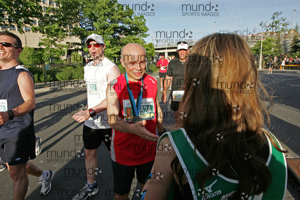 (Ottawa, ON --- May 29, 2010) VINCE CAMPANELLI receiving his medal after finising the 10km race during the Ottawa Race Weekend. Photograph copyright Sean Burges / Mundo Sport Images