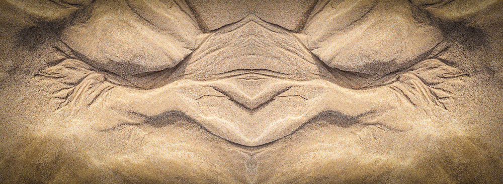 I took an photograph of sand carved by the retreating tide, made a mirror image, and combined them into this face-like image