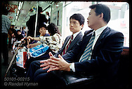 Businessmen sit and talk on local train to Ueno station in Tokyo. Japan