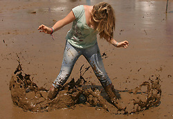 © Licensed to London News Pictures. 24/06/2012. Somerset, UK. A woman splashes the mud wearing wellington boots. Festival goers enjoy the mud and the sunshine at The Sunrise Festival held at Bruton In Somerset today 24 June 2012. Photo credit : Jason Bryant/LNP