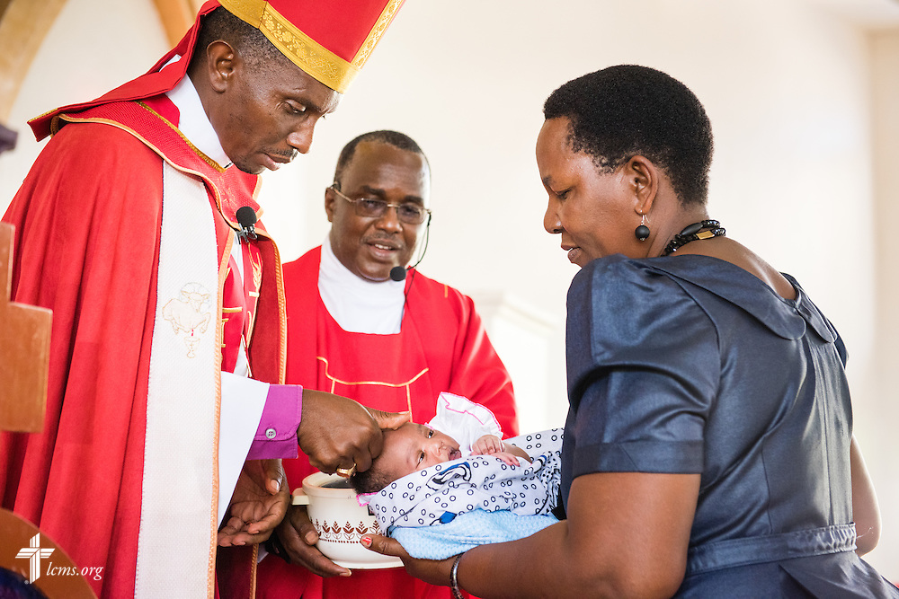 Bishop Emmanuel Makala baptizes a baby as deaconess Scholastica Bubembwas holds the infant on Sunday, March 15, 2015, at the Evangelical Lutheran Church in Tanzania – South-East of Lake Victoria Diocese's (ELCT-SELVD) Ebenezer Cathedral in Shinyanga, Tanzania. LCMS Communications/Erik M. Lunsford