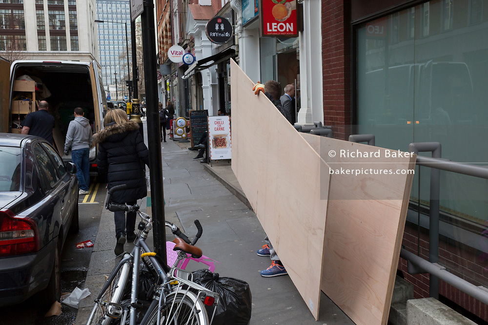 A construction workman places another board sheeting with others on a West End street, on 4th March 2019, in London England.