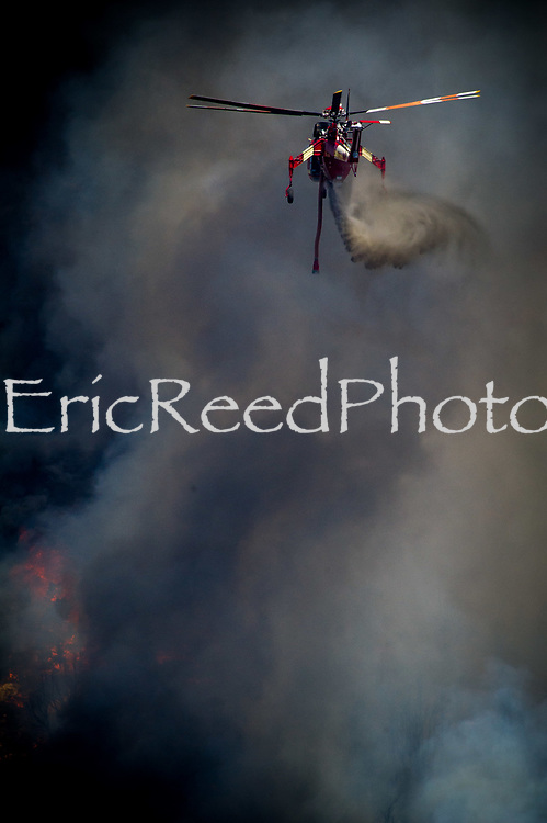 A fire fighting helicopter drops water on The Holcomb Fire as it burns in the Holcomb Valley are of the San Bernardino National Forest near Big Bear, Tuesday, June 20, 2017. Firefighters are battling a wildland fire north of Baldwin Lake in the Big Bear Lake area had charred 950 acres, and was 10 % contained. (EricReed/For The Souther California Newspaper Group)