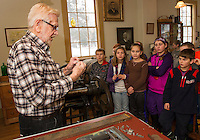 Walt Stockwell describes the job of a printer during colonial times in the Grange store during Gilford Elementary School's 4th grade Colonial Life and Tradesman walking field trip on Thursday morning.  (Karen Bobotas/for the Laconia Daily Sun)