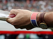 A man wearing an American flag wrist band holds onto a full-field sized American flag that is stretched over the field in memory of the lives lost on the 15th anniversary of the 9/11 terror attack on the United States before the Philadelphia Eagles 2016 NFL week 1 regular season football game against the Cleveland Browns on Sunday, Sept. 11, 2016 in Philadelphia. The Eagles won the game 29-10. (©Paul Anthony Spinelli)