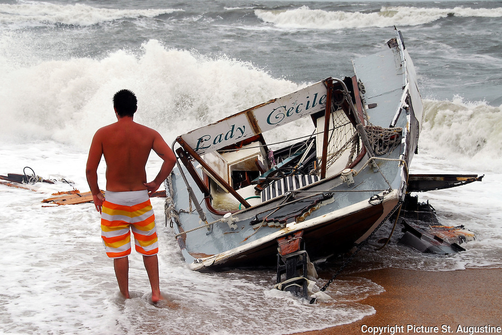 Hurricane Season -Destroyed by Fay. A young man studies what is left of a 65 foot schooner sailboat that was left, High and Dry on Vilano Beach in St. Augustine, Florida.  The Captain had attempted to negotiate the extremely rough St. Augustine Inlet in the build up to Tropical Storm Fay.