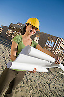 Young woman examining blueprint in construction site